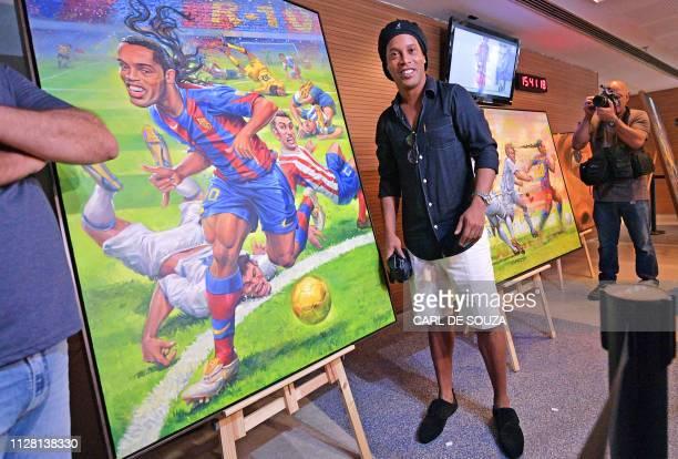 Brazilian former footballer Ronaldinho poses next to a paining by artist Emerson Carvalho de Souza during a photocall to unveil memorabilia and...