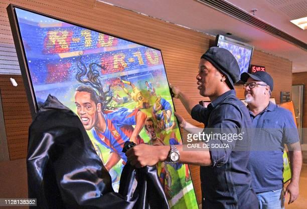 TOPSHOT Brazilian former footballer Ronaldinho unveils a painting by artist Emerson Carvalho de Souza during a photocall to unveil memorabilia and...