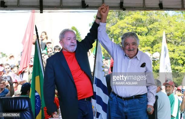 Brazilian former president Luiz Inacio Lula da Silva and Uruguay's former president Jose Mujica acknowledge supporters during a meeting in Santana do...