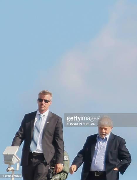 Brazilian former president Luiz Inacio Lula da Silva is escorted as he arrives at the Federal Police headquarters in Curitiba Parana state Brazil...