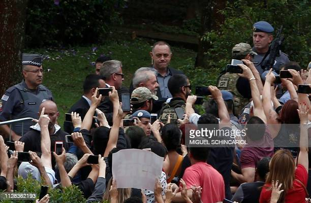 Brazilian former president Luiz Inacio Lula da Silva is escorted by security forces upon arrival at Jardim da Colina cemetery, in Sao Bernardo do...