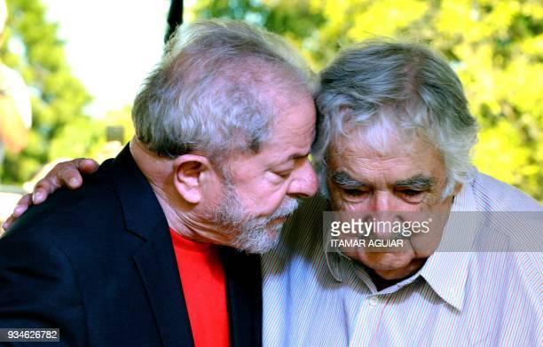 Brazilian former president Luiz Inacio Lula da Silva speaks with Uruguay's former president Jose Mujica during a meeting in Santana do Livramento...