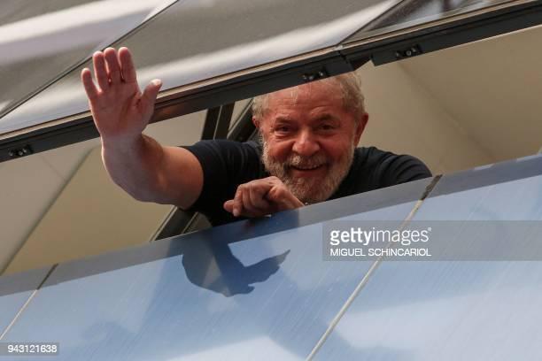 TOPSHOT Brazilian former president Luiz Inacio Lula da Silva waves from a window of the Metallurgical Union in Sao Bernardo do Campo Sao Paulo state...