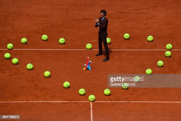 Brazilian former tennis player Gustavo Kuerten poses in the middle of the heart shaped with tennis balls before men's final tennis match at the...