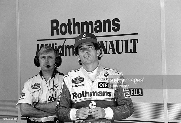 Brazilian Formula 1 race car driver Ayrton Senna and a team mechanic watch a qualifying round of the San Marino F1 Grand Prix on the Imola Circuit...