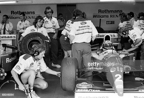 Brazilian Formula 1 race car driver Ayrton Senna sits in his car as team mechanics prepare it for a qualifying round of the San Marino F1 Grand Prix...