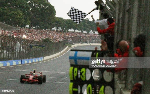 Brazilian Formula One driver Felipe Massa gets the chequered flag winning the Brazilian Gran Prix at the Interlagos racetrack in Sao Paulo Brazil on...