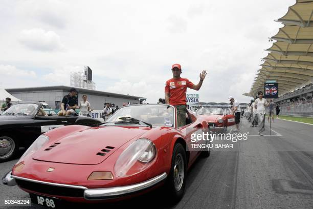 Brazilian Formula One driver Felipe Massa of Ferrari waves from a vintage Ferrari Dino sports car during the drivers' track parade on race day for...