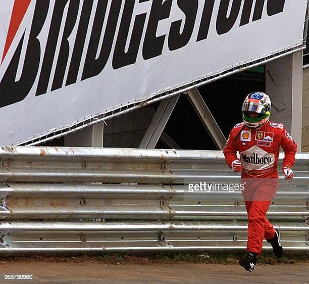 Brazilian Formula One driver Rubens Barrichello runs back to the pits of Ferrari to take the second car after experiencing an engine problem during...