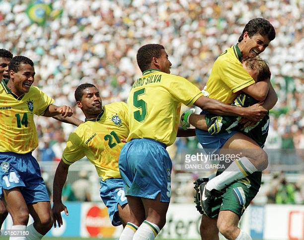 Brazilian forward Bebeto jumps to hug goalkeeper Claudio Taffarel as teammates Cafu Viola and Mauro Silva move in after Italian Roberto Baggio missed...