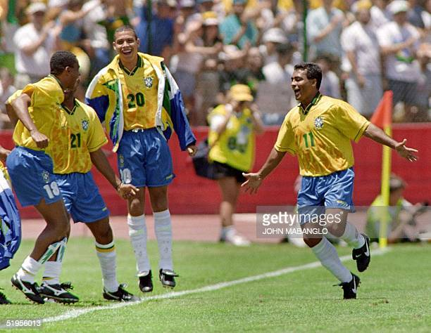 Brazilian forward Romario runs towards his teammates Paulo Sergio Viola and Ronaldo after scoring a goal against Russia 21 June 1994 in Stanford...