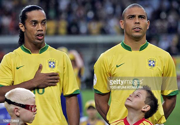 Brazilian forward Ronaldo and midfielder Ronaldinho listen to their national Anthem prior to the opening round Group F World Cup football match Japan...