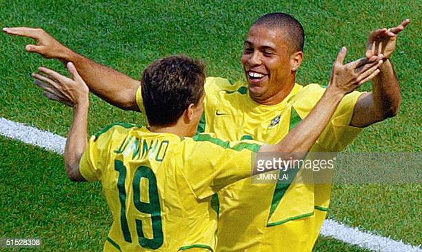 Brazilian forward Ronaldo celebrates after scoring the second goal for his team with teammate midfielder Juninho during their Group C match against...