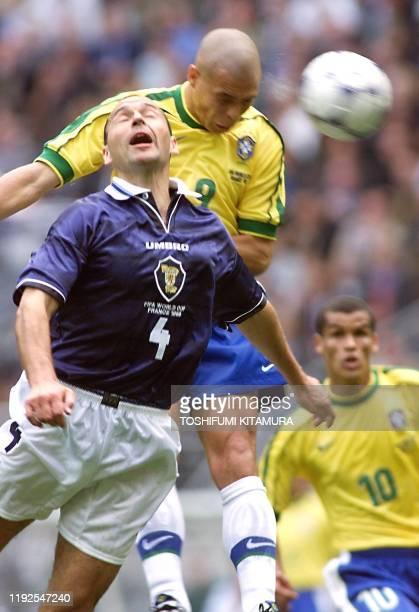 Brazilian forward Ronaldo heads off the ball over Scottish defender Colin Calderwood 10 June at the Stade de France in Paris during their 1998 Soccer...