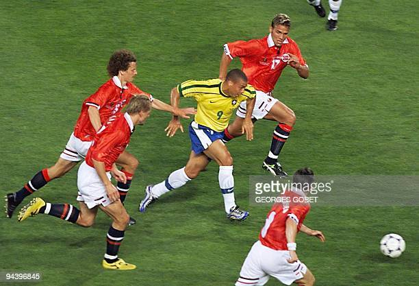 Brazilian forward Ronaldo is challenged by Norwegian forward Havard Flo defender Dan Eggen midfielder Kjetil Rekdal and midfielder Oyvind Leonhardsen...