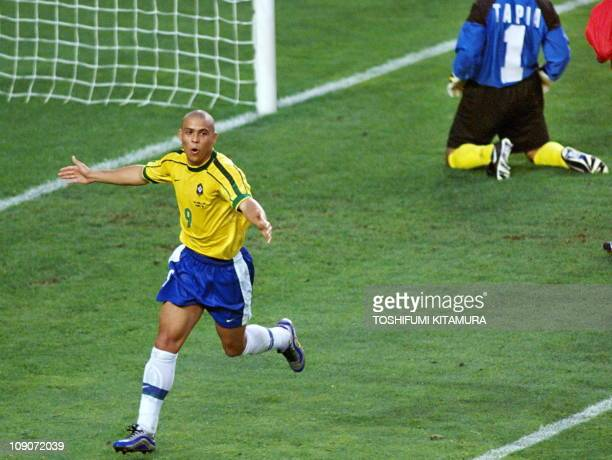 Brazilian forward Ronaldo jubilates as Chilean goalkeeper Nelson Tapia kneels on the pitch after scoring the third goal for his team when French...