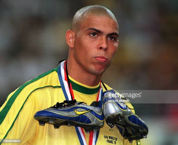 Brazilian forward Ronaldo wears his shoes tied up around his neck and looks disappointed after the 1998 World Cup soccer game France against Brazil...