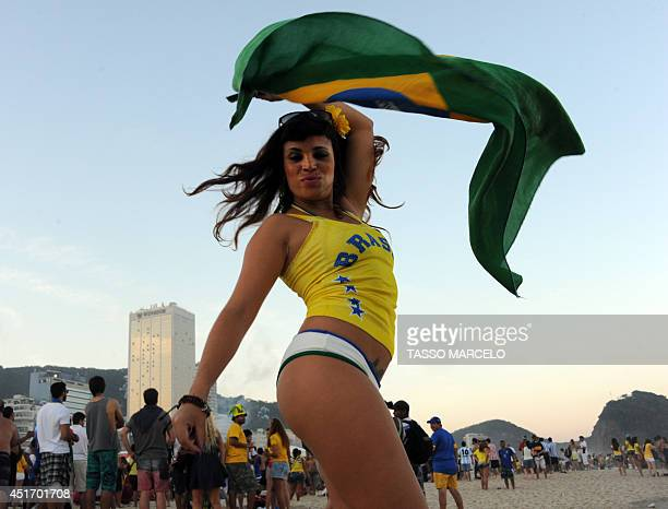 A Brazilian girl waves a flag at the Fan Fest in Copacabana beach in Rio de Janeiro Brazil on July 4 2014 during the 2014 FIFA World Cup Brazil vs...