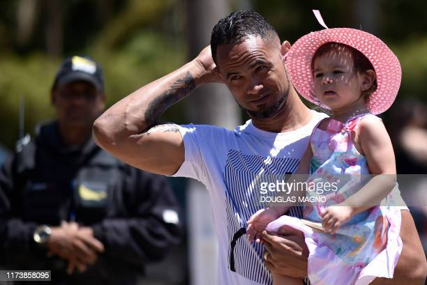 Brazilian goalkeeper Bruno attends his presentation as new goalkeeper of the Pocos de Caldas Football Club with his daughter Isabela in Pocos de...