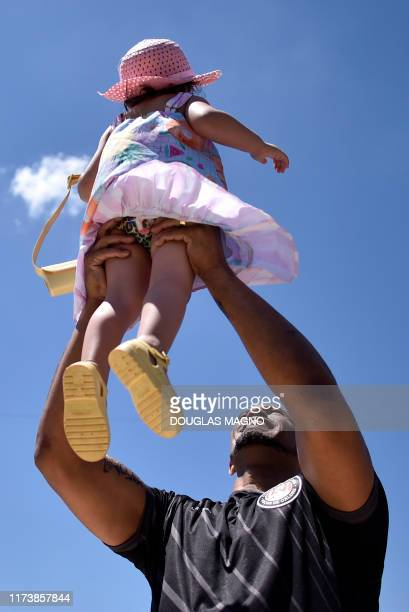 Brazilian goalkeeper Bruno holds up his daughter Isabela during his presentation as new goalkeeper of the Pocos de Caldas Football Club in Pocos de...