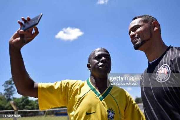 Brazilian goalkeeper Bruno poses for selfie with a fan during his presentation as new goalkeeper of the Pocos de Caldas Football Club in Pocos de...