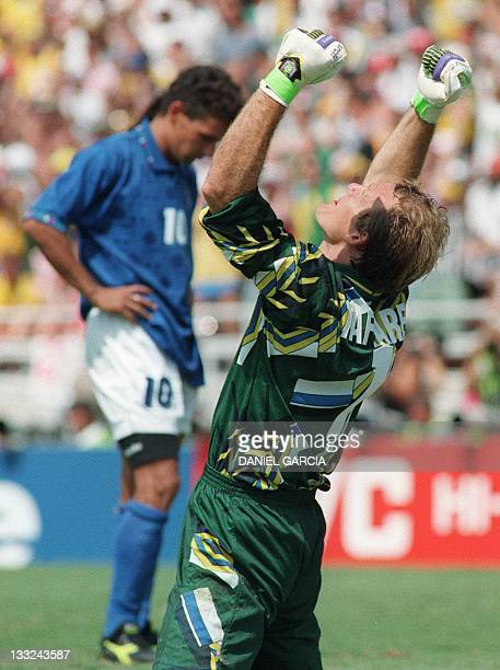 Brazilian goalkeeper Claudio Taffarel pumps his fists in the air after Italian forward Roberto Baggio missed his penalty kick at the end of the...