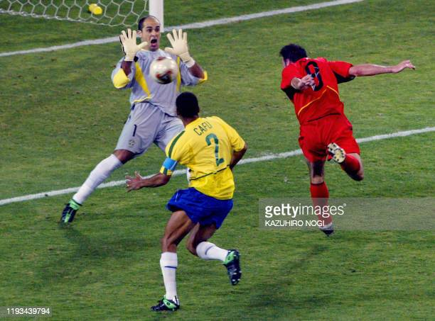 Brazilian goalkeeper Marcos saves a header from Belgian midfielder Bart Goor as Brazilian defender cafu looks on during the second round match...