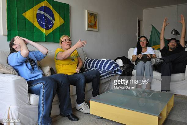A Brazilian group of friends are watching the fifa Worldcup 2014 match brazil x chile at home