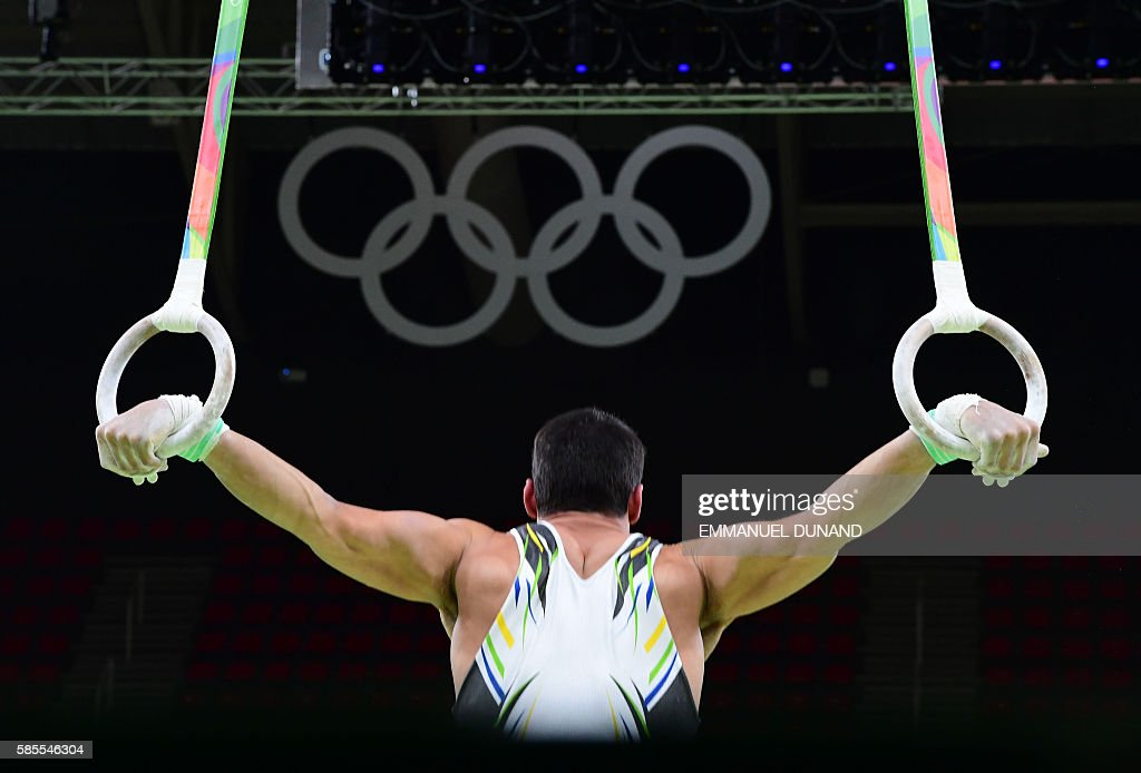 Brazilian gymnast practices on the rings of the men's Artistic gymnastics during a practice session at the Olympic Arena on August 3, 2016 ahead of the Rio 2016 Olympic Games in Rio de Janeiro. / AFP / Emmanuel DUNAND