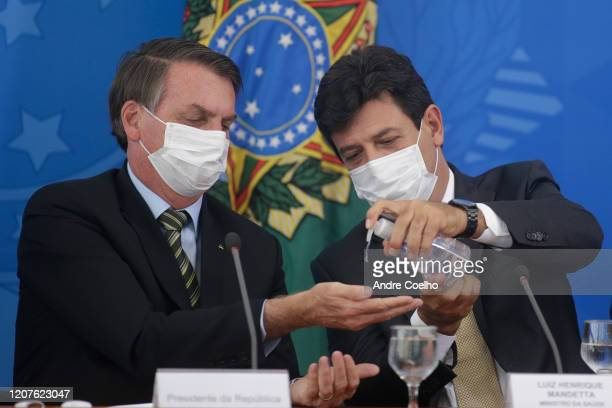 Brazilian Health Minister Luiz Henrique Mandetta gives gel alcohol to President of Brazil Jair Bolsonaro both using protective masks during a press...
