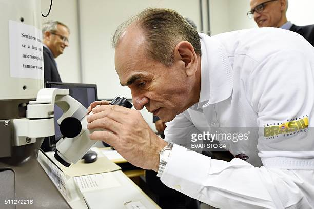 Brazilian Health Minister Marcelo Castro looks at the Zika virus through a microscope during a visit to the Biological Sciences Institute at the...