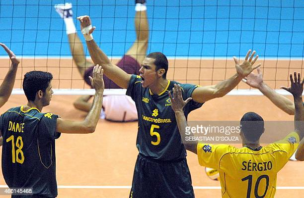Brazilian Henrique celebrates with teammates Sergio and Dante in the final seconds of the set during the volleyball championship against Venezuela 29...