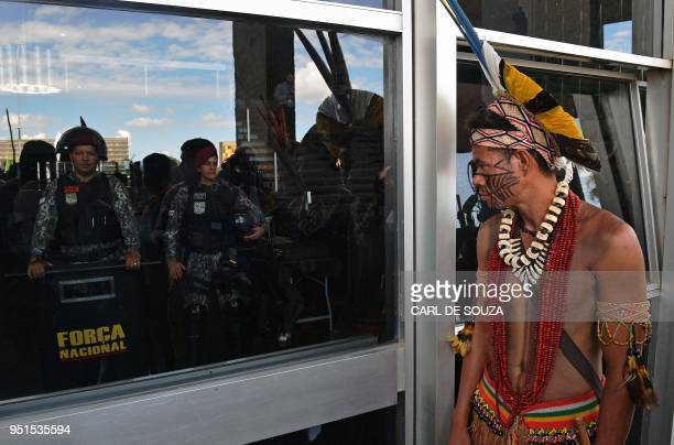 A Brazilian indigenous man looks at riot police through the window of a government building during a protest in Brasilia on April 26 2018...