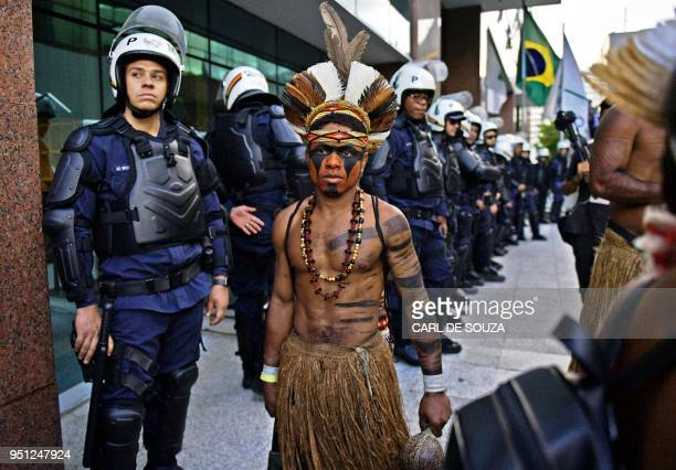 A Brazilian indigenous man walks past riot police during a protest against the government's decision not to recognize the land demarcation of...