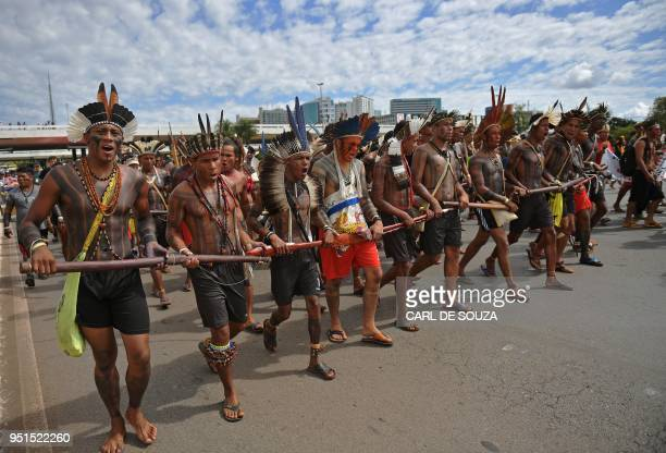 Brazilian indigenous men march towards the government's buildings during a protest in Brasilia on April 26 2018 Approximately 2500 indigenous people...