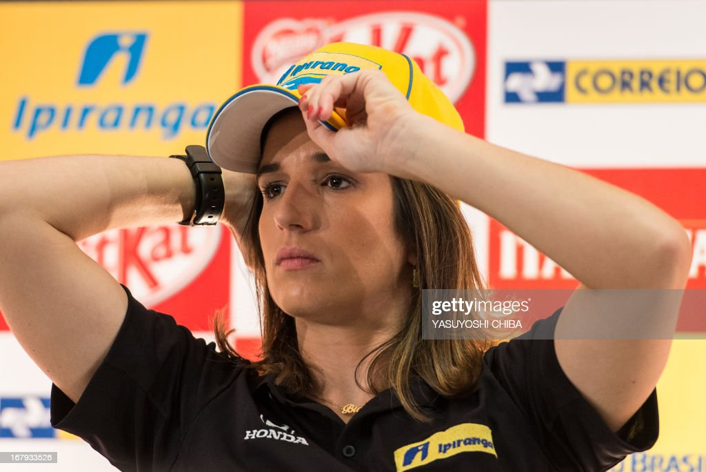 Brazilian IndyCar driver Bia Figueiredo adjusts her cap during a press conference in Sao Paulo, Brazil on May 2, 2013. The Itaipava Indy 300 Nestle race will be held on May 5. AFP PHOTO/Yasuyoshi CHIBA