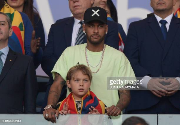 Brazilian injured footballer Neymar and his son Davi Lucca are seen on the stands before the Copa America football tournament final match between...