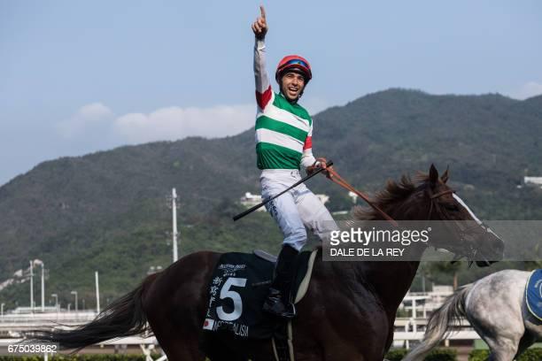 Brazilian jockey Joao Moreira onboard Neorealism celebrates after winning the Audemars Piguet QEII Cup horse race at Sha Tin race course in Hong Kong...