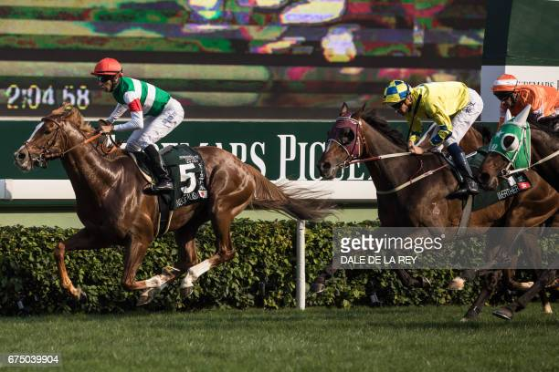 Brazilian jockey Joao Moreira onboard Neorealism crosses the finish line to win the Audemars Piguet QEII Cup horse race at Sha Tin race course in...