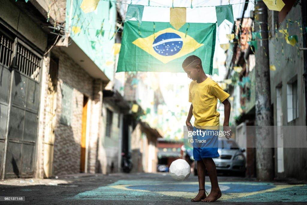 Braziliaanse Kid te voetballen in de straat : Stockfoto