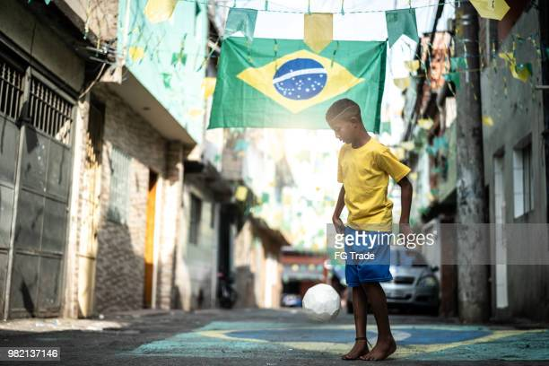 brazilian kid playing soccer in the street - brazil stock pictures, royalty-free photos & images