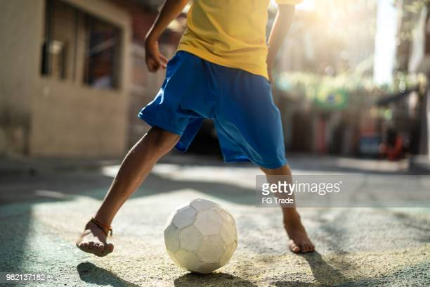brazilian kid playing soccer in the street - brasil stock pictures, royalty-free photos & images