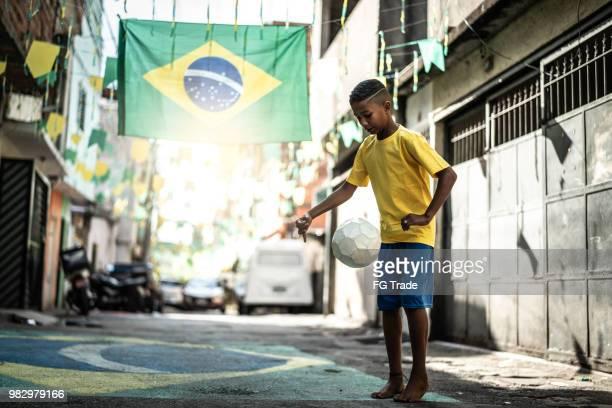 garoto brasileiro jogando futebol na rua - evento de futebol internacional - fotografias e filmes do acervo