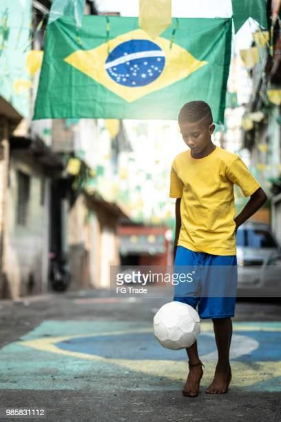 brazilian kid playing soccer in the street - favela imagens e fotografias de stock