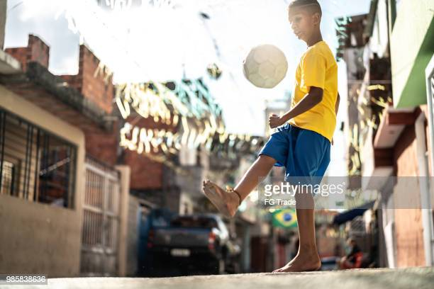 brazilian kid playing soccer in the street - favela stock pictures, royalty-free photos & images