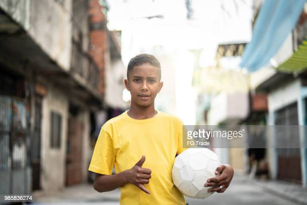 brazilian kid playing soccer portrait - favela stock pictures, royalty-free photos & images