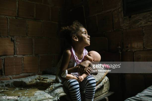 brazilian little girl holding a doll in the bedroom - poverty stock photos and pictures