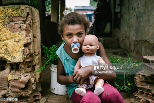 menina brasileira segurando uma boneca - pobreza questão social - fotografias e filmes do acervo