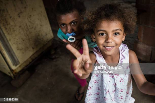 brazilian little girl making two or v sign with her fingers - favela stock pictures, royalty-free photos & images