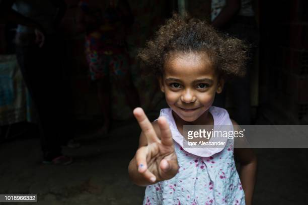 brazilian little girl making two or v sign with her fingers - animal finger stock photos and pictures